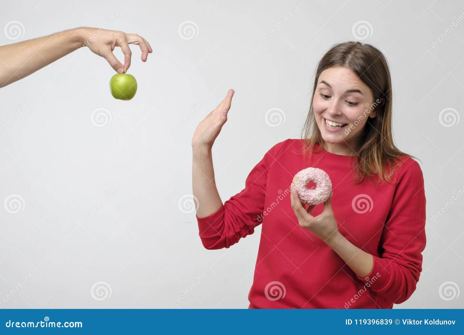 Comida sana y concepto de la dieta Mujer joven hermosa que elige entre las frutas y los dulces