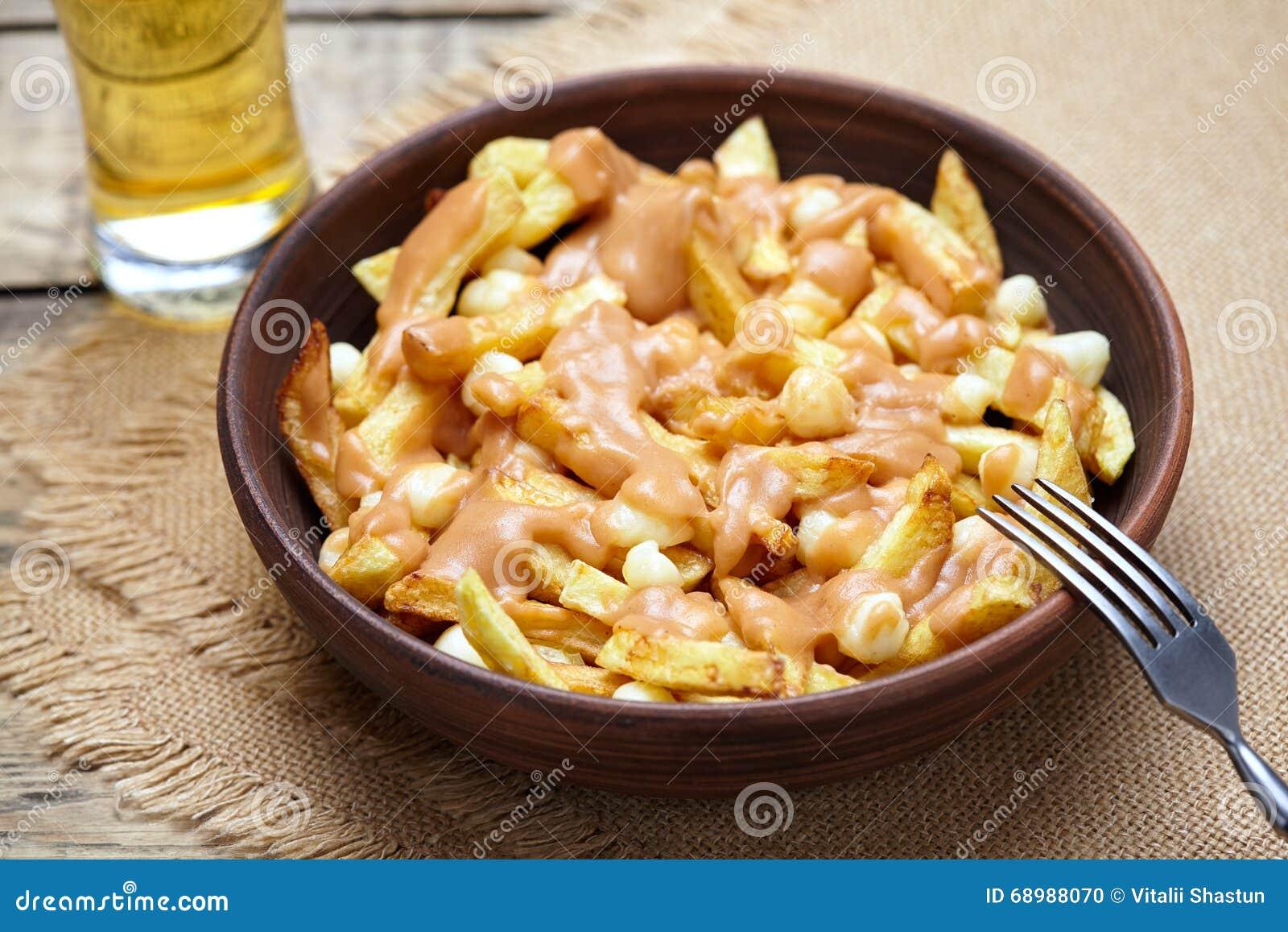 Comida tradicional de Poutine Quebec con las fritadas, el queso cuajado y la salsa