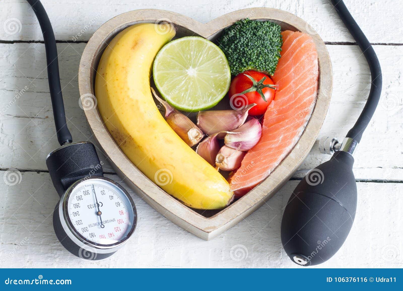 Comida y concepto sano de la dieta del corazón con el indicador del preasure de la sangre en los tablones blancos