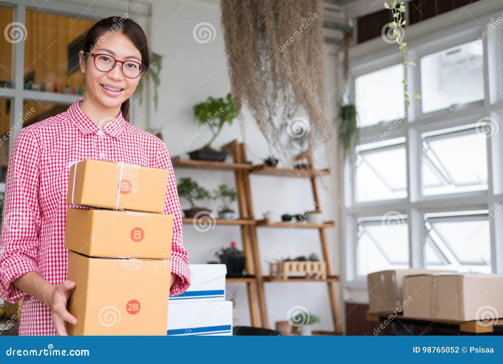 Commencez le petit entrepreneur tenir la boîte de colis sur le lieu de travail f