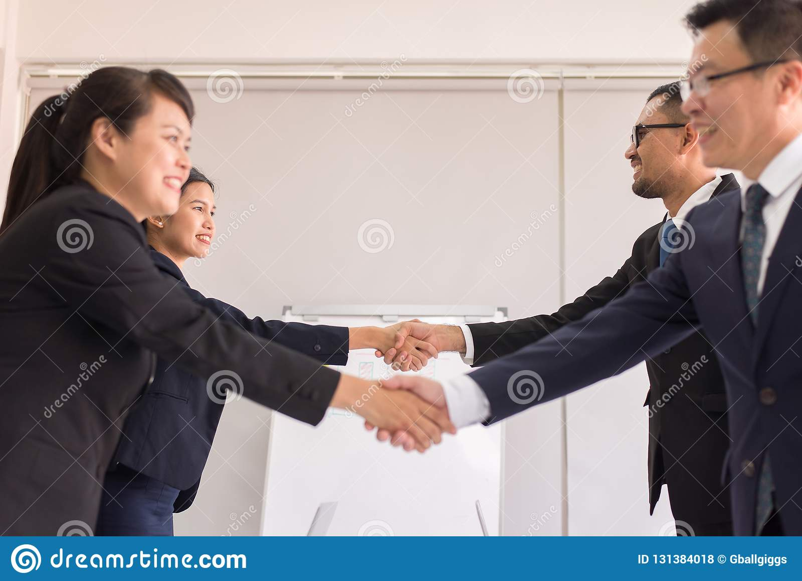 Commerciële team Aziatische mensen die in formele kostuum het schudden handen omhoog eindigen samenkomend, Selectieve nadruk, Gel