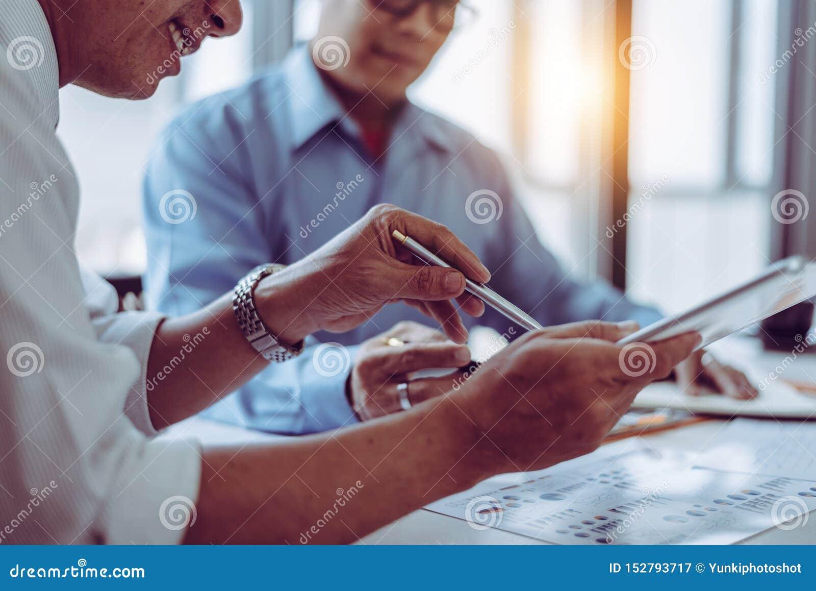 Commerciële vergaderings Aziatische mensen twee mannelijke midden-leeftijd die terwijl samen het zitten bespreken