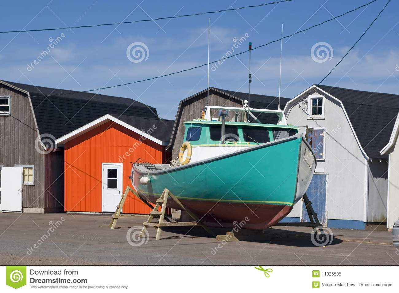 Commercial lobster boat outside colorful bait sheds prior to launching ...