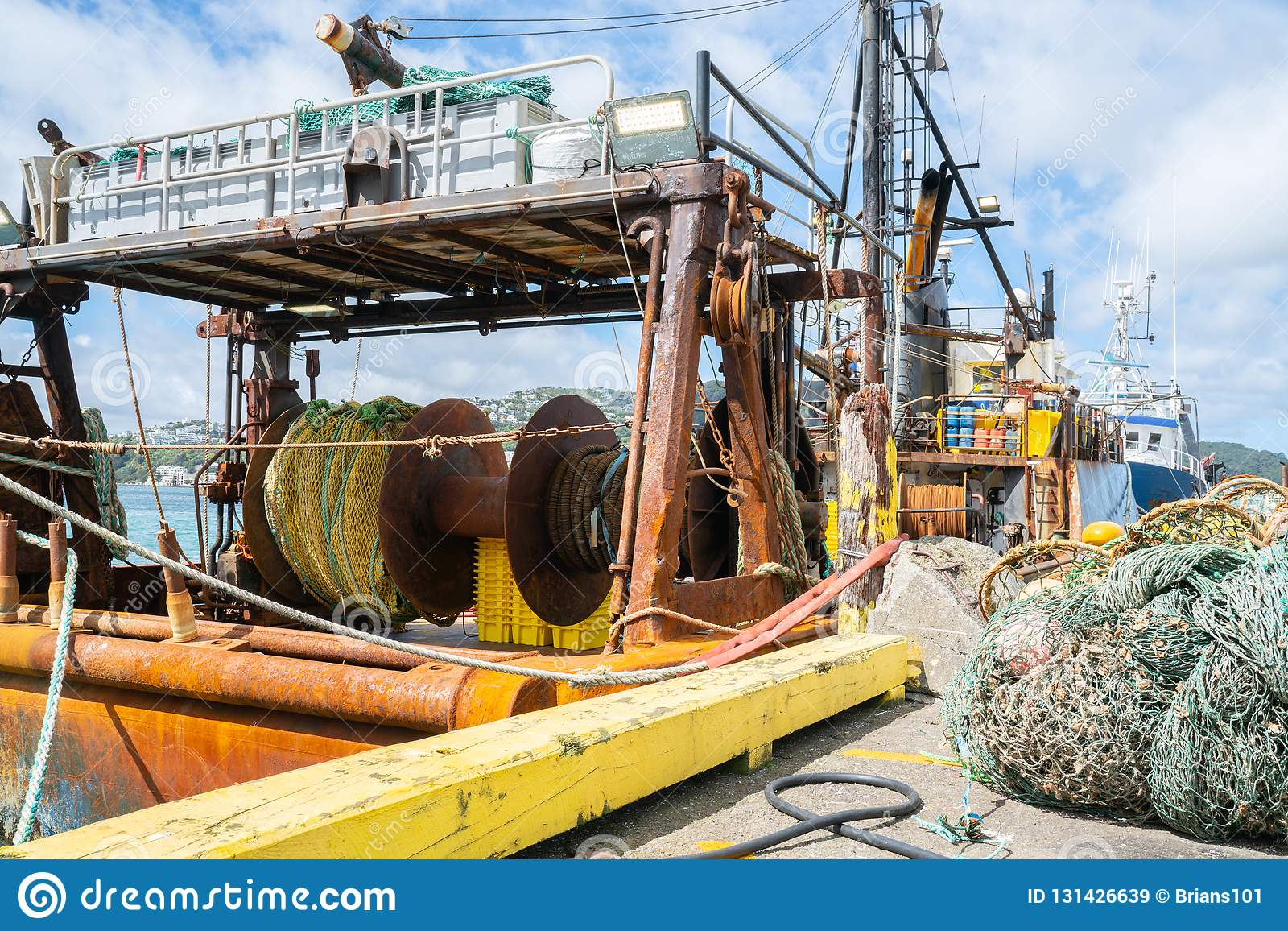 Commercial Fishing Boats Gear And Nets Moored At Wharf