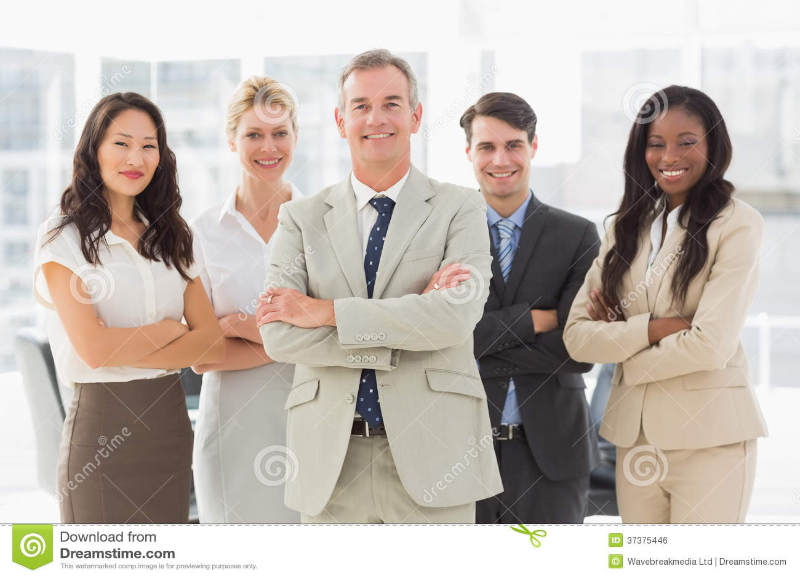 Commercieel team die bij camera met gevouwen wapens glimlachen