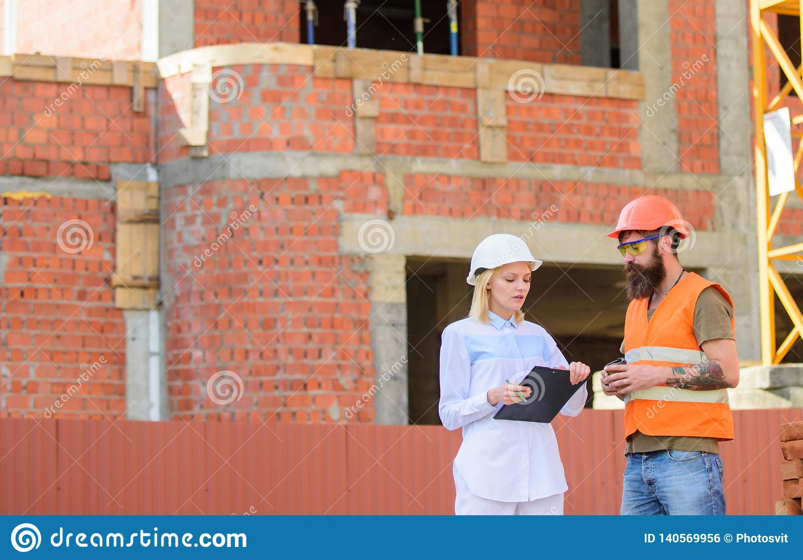 Communicatie van het bouwteam concept Bespreek vooruitgangsplan De de vrouweningenieur en bouwer delen bouwwerf mee