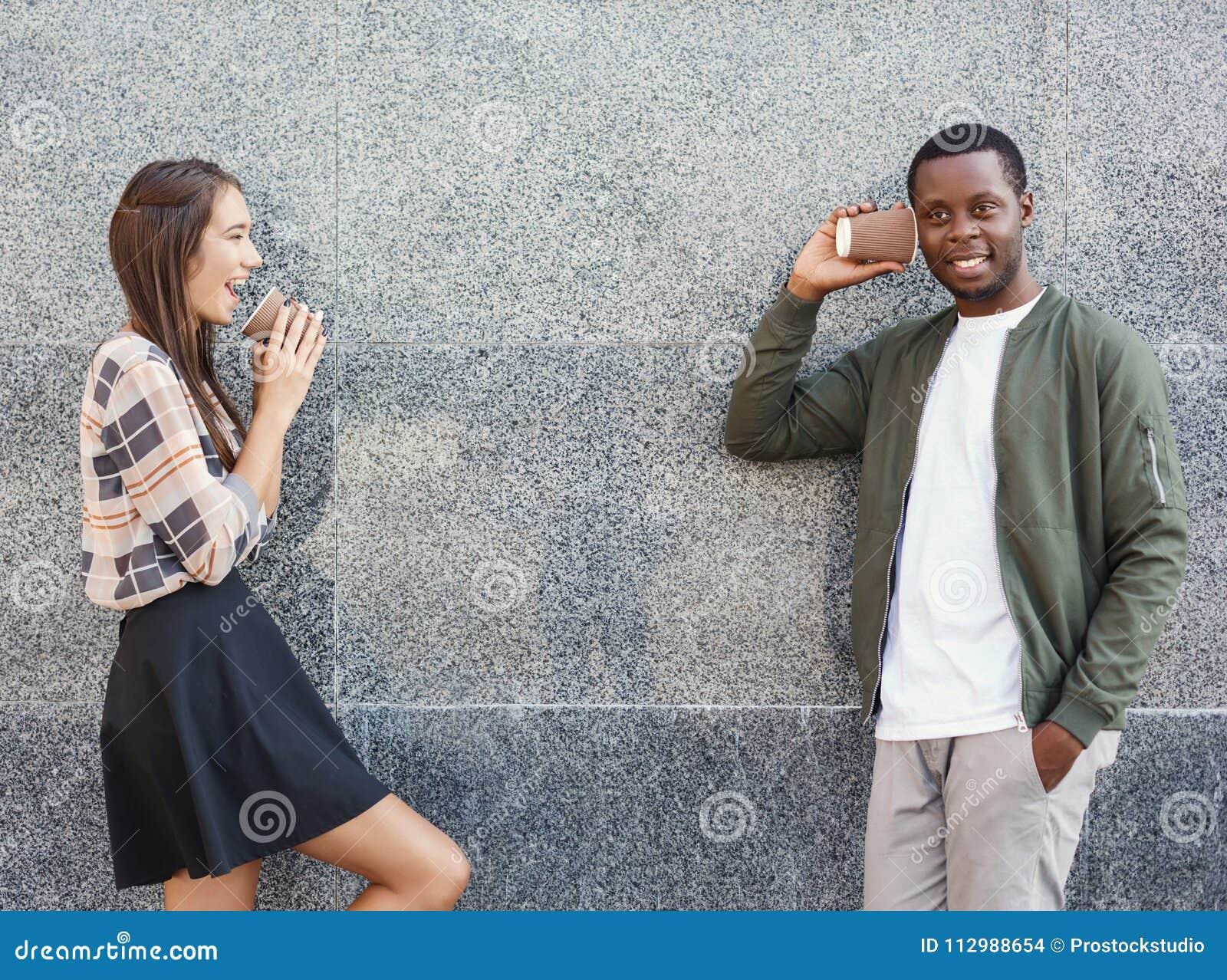 Multiracial couple talking through tin can phone