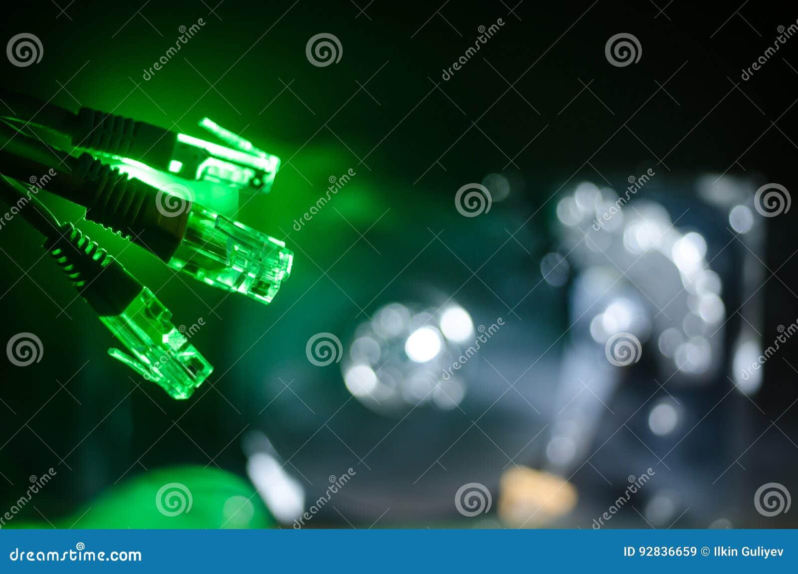 Commutatore di rete e cavi di Ethernet, simbolo delle comunicazioni globali La rete colorata cabla su fondo scuro con le luci e l