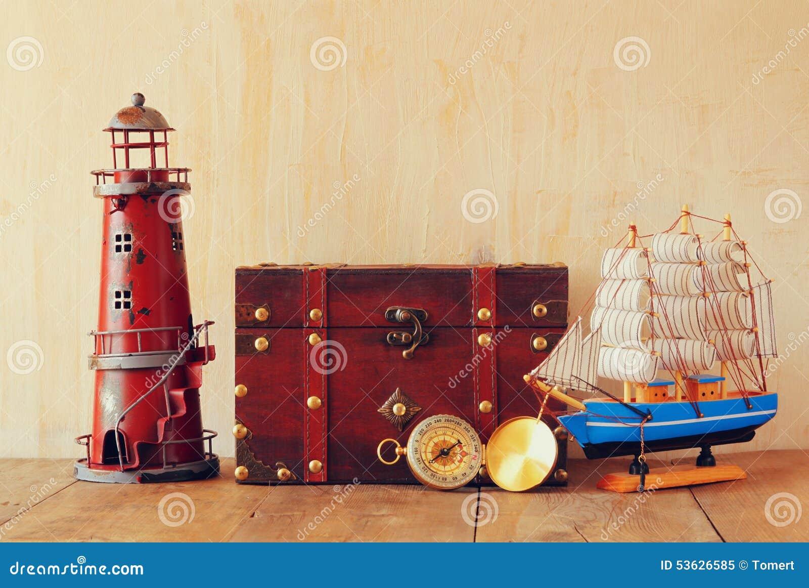 Compás antiguo, faro del vintage, barco de madera y pecho viejo en la tabla de madera