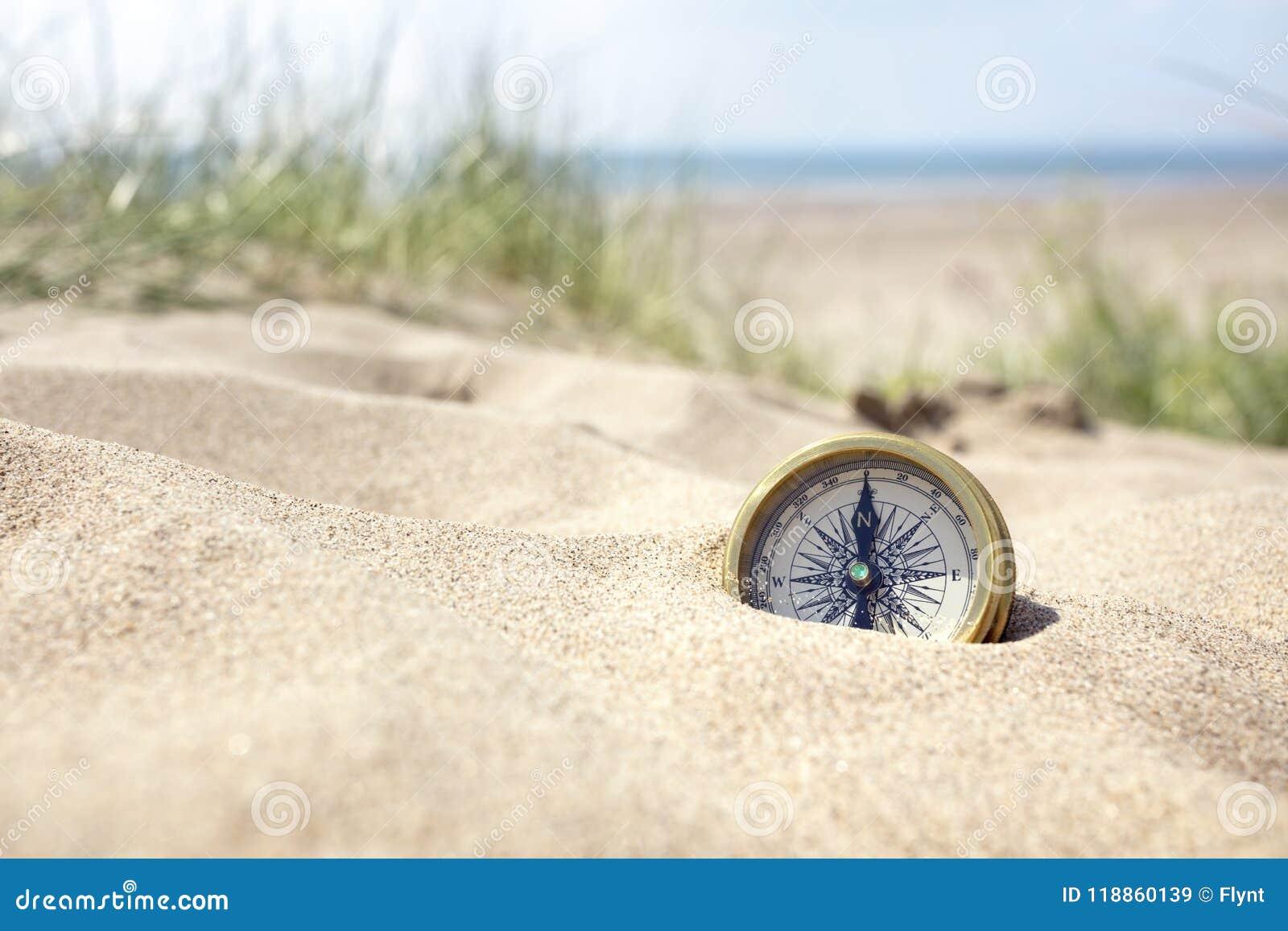 Compás en la playa con la arena y el mar