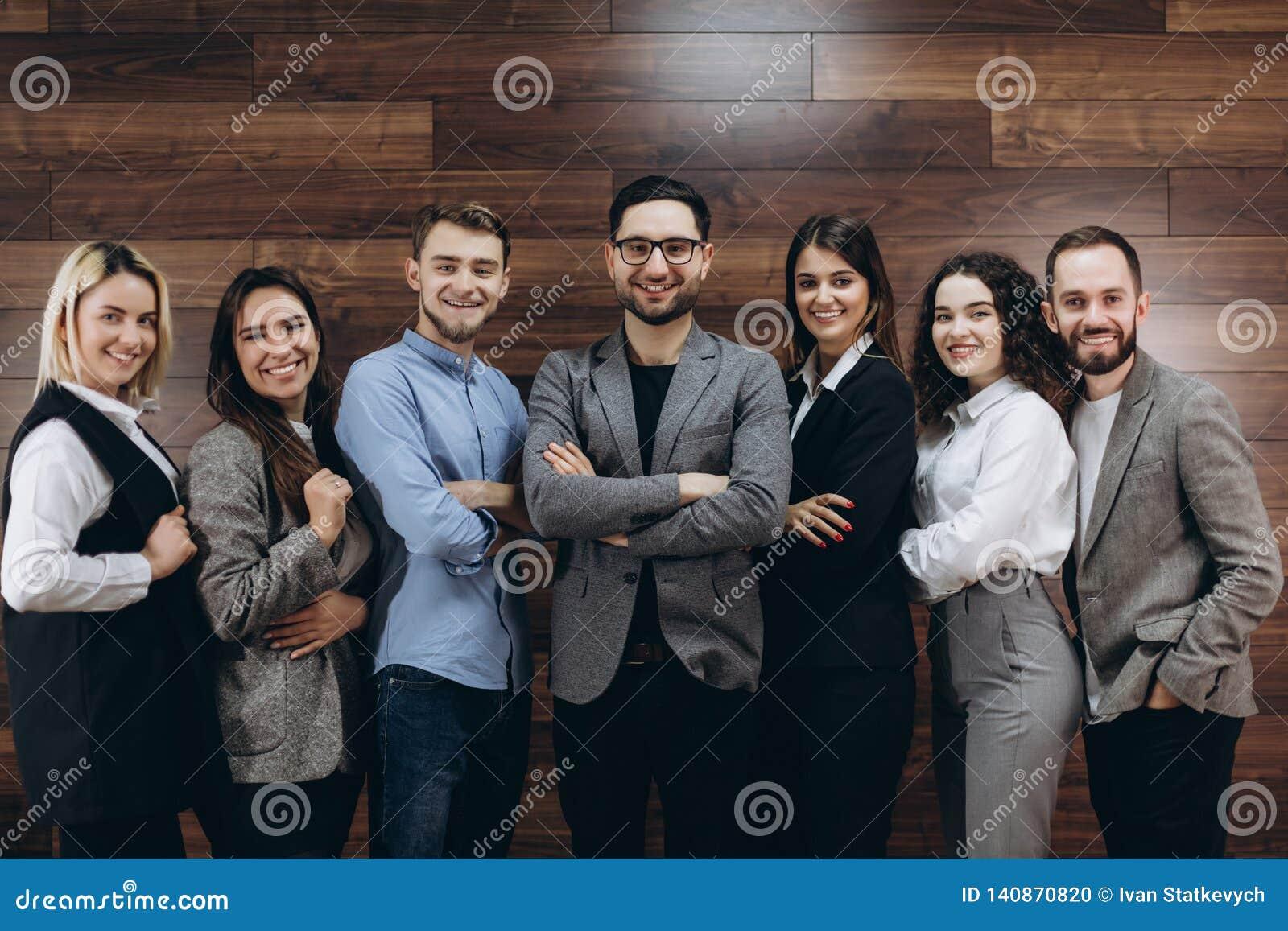 Compañía acertada con los trabajadores felices que se colocan en fila en oficina moderna
