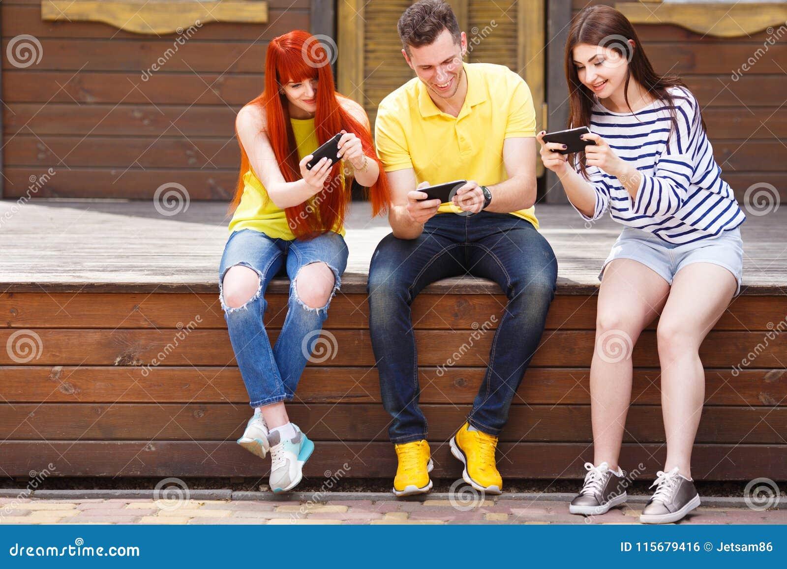 Compañía de tres miembros que juegan a juegos móviles