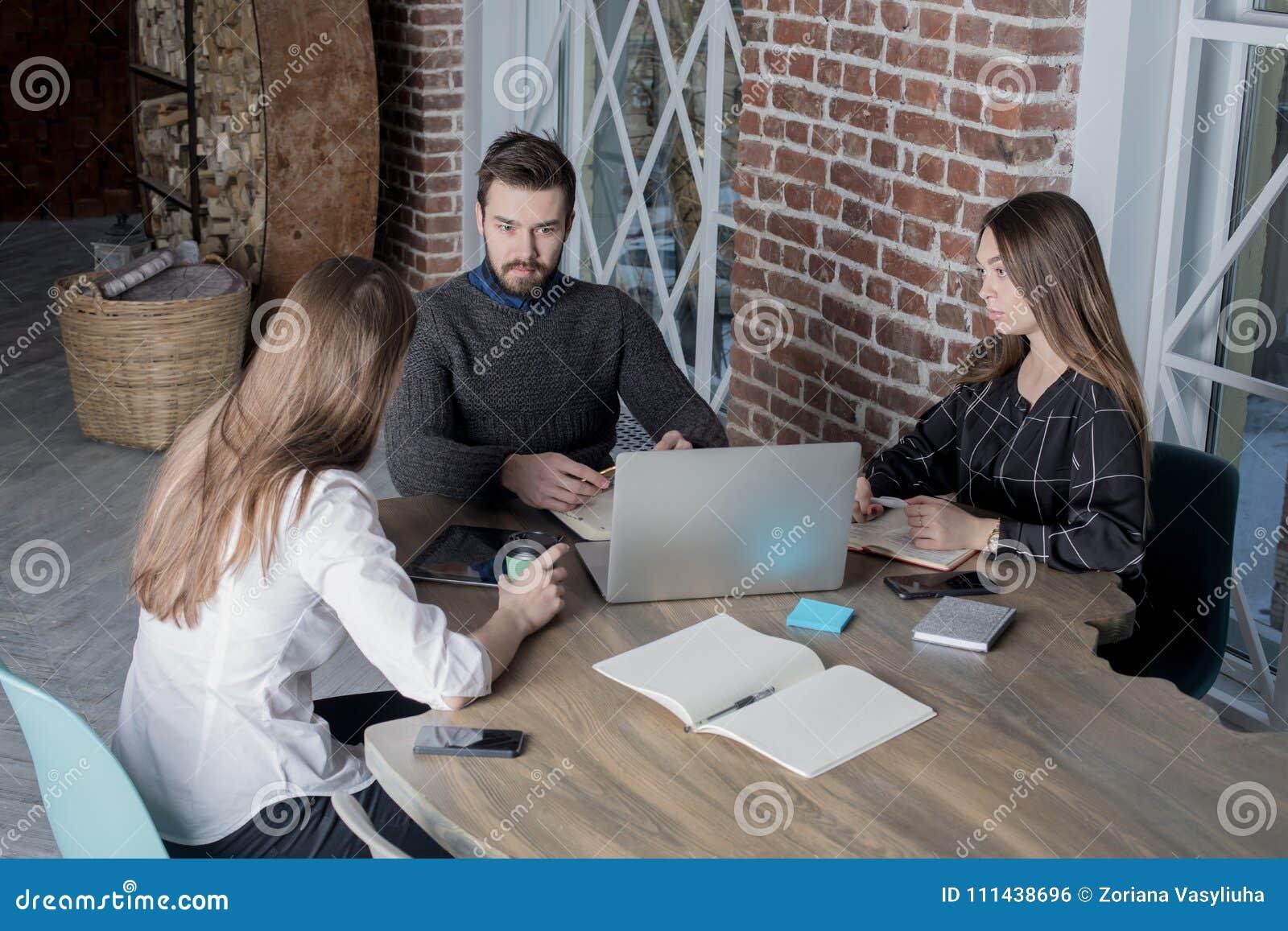 Compañeros de trabajo jovenes que tienen curso de aprendizaje usando el ordenador portátil moderno para la información de ahorro