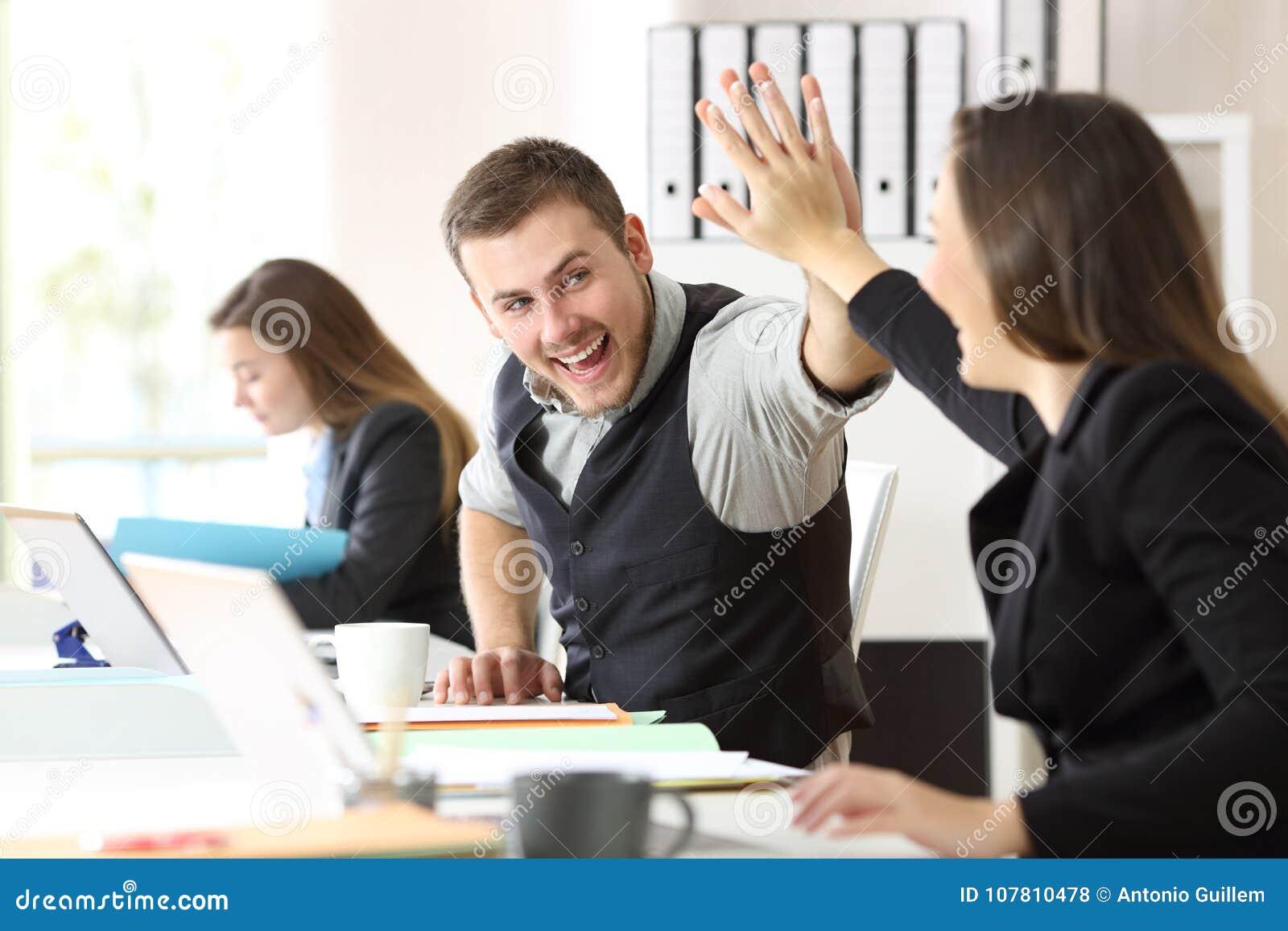 Compañeros de trabajo que celebran el logro en la oficina