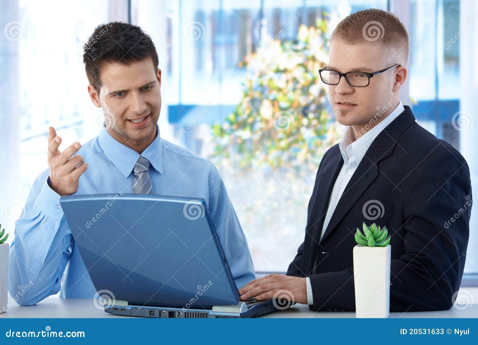 Compa eros de trabajo que discuten el trabajo en oficina for Que es trabajo de oficina