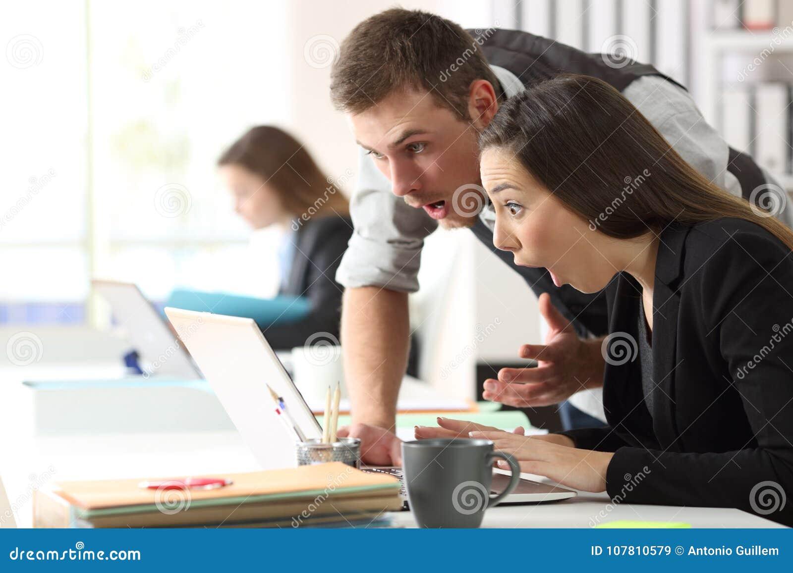 Compañeros de trabajo sorprendidos que leen en la línea noticias en la oficina
