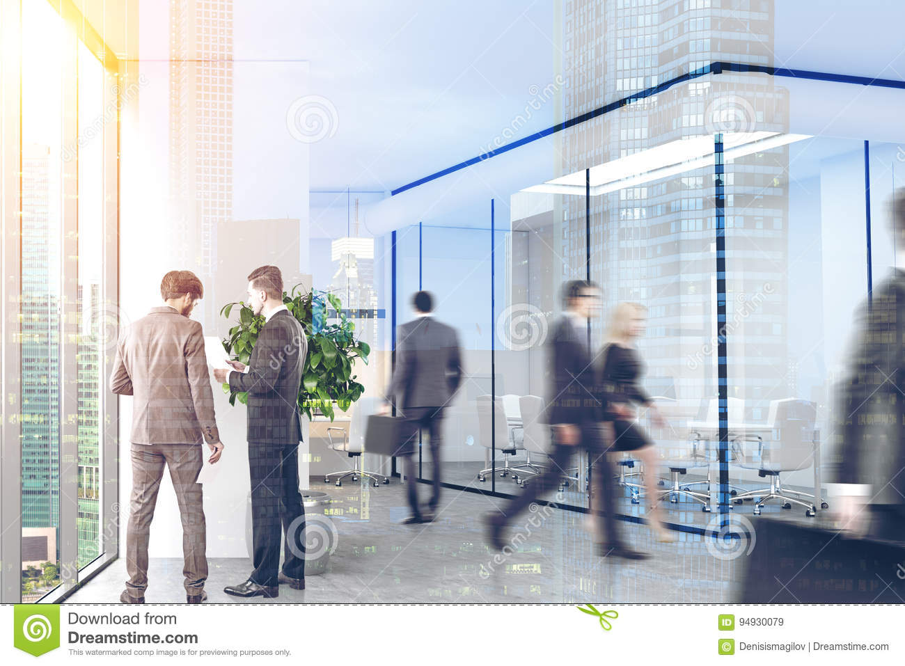 7fedf33e01ba Company employees are walking and talking in a modern office with white and  glass walls