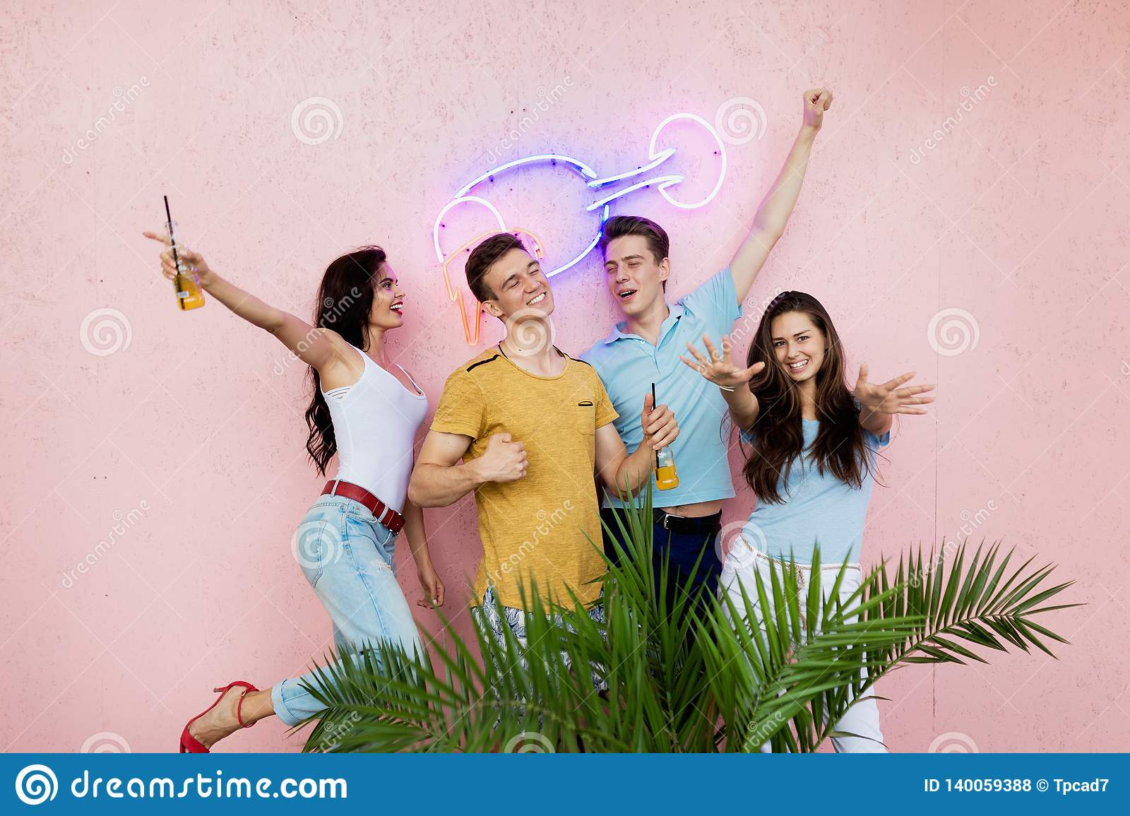 A company of good-looking friends laughing, drinking yellow cocktails is standing in front of the pink wall and behind a