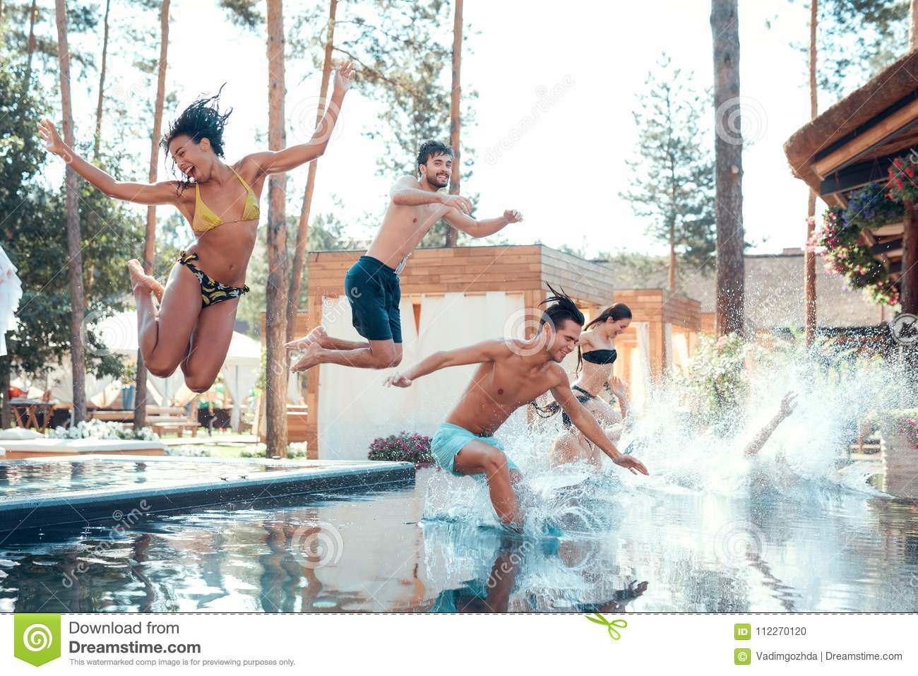 Company of happy young people jumping in pools forming splashes. Swimming pool party concept.