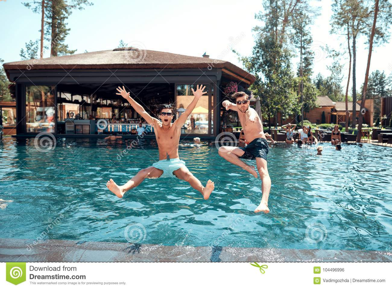 Young guys and girls jump into the pool.