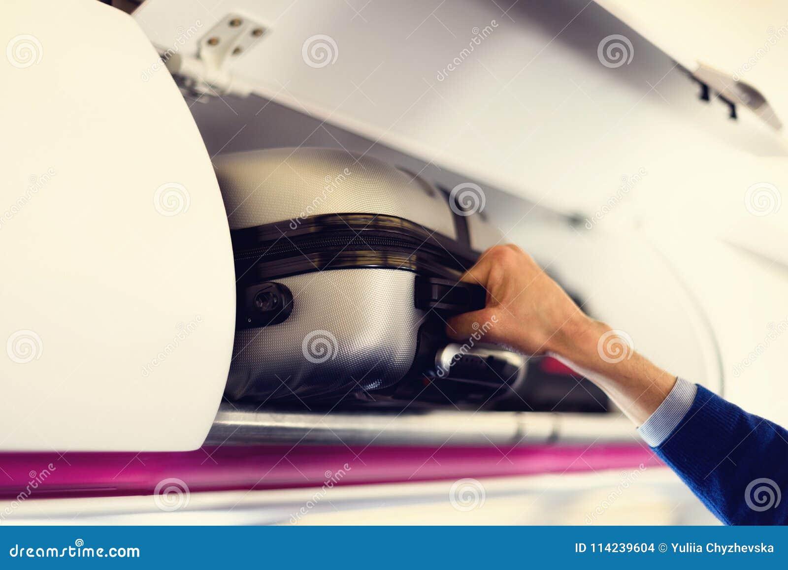 Compartiment de Main-bagage avec des valises dans l avion Les mains enlèvent le bagage de main Le passager a mis la carlingue de