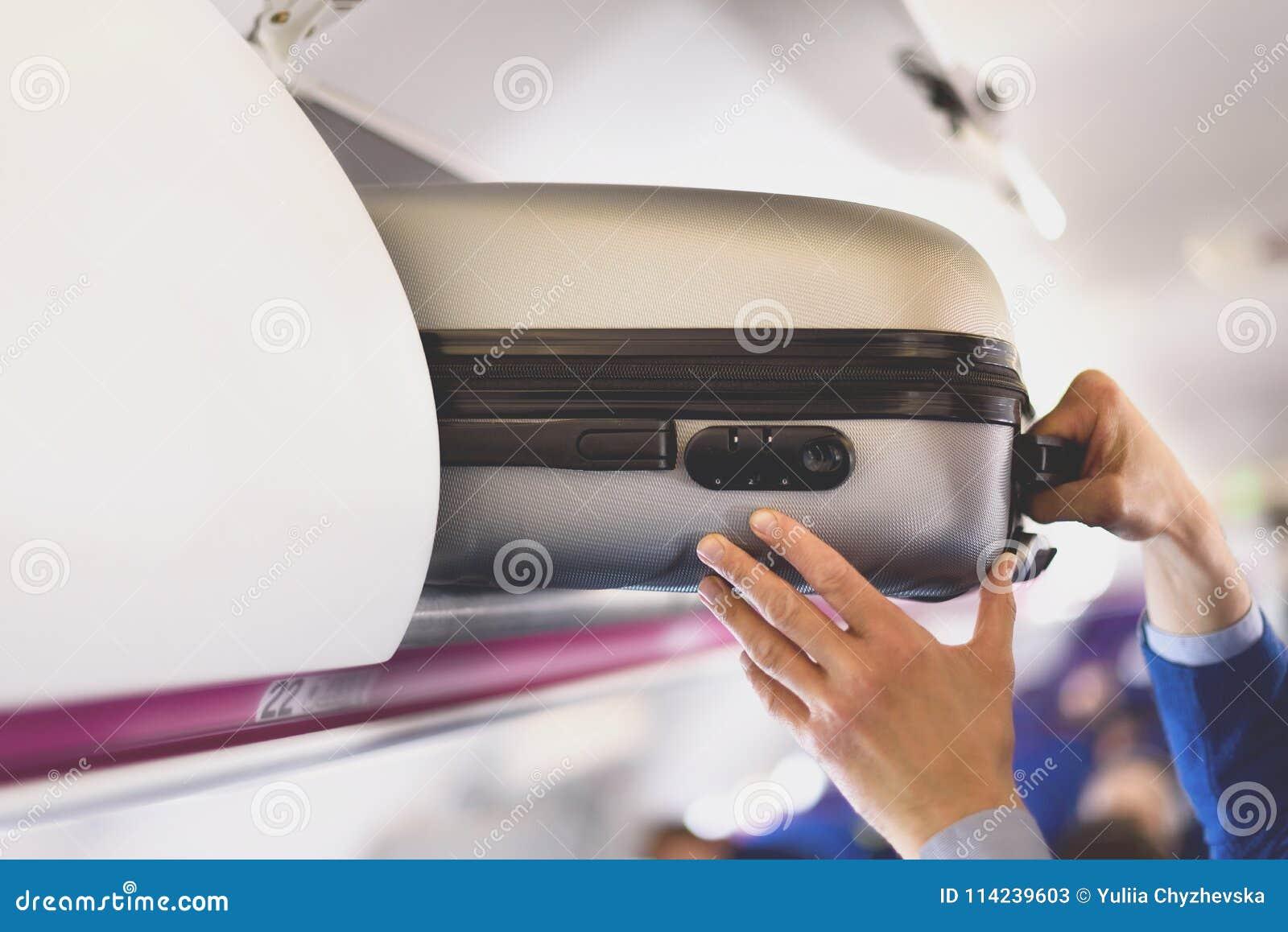 Compartimento da Mão-bagagem com as malas de viagem no avião As mãos decolam a bagagem de mão O passageiro pôs a cabine do saco d