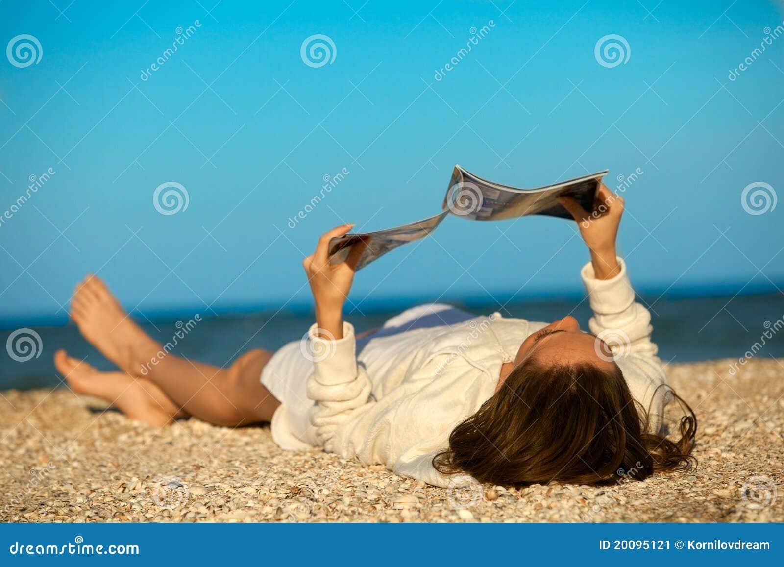 Compartimiento de la lectura de la mujer en la playa