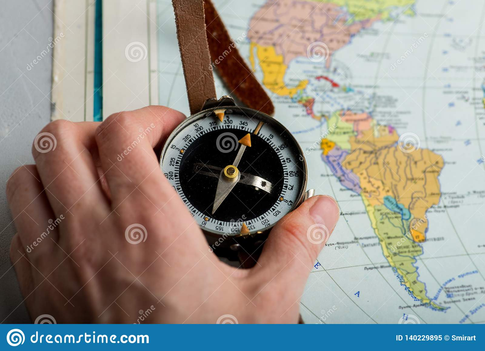 Compass in hand against the background of a bright world map