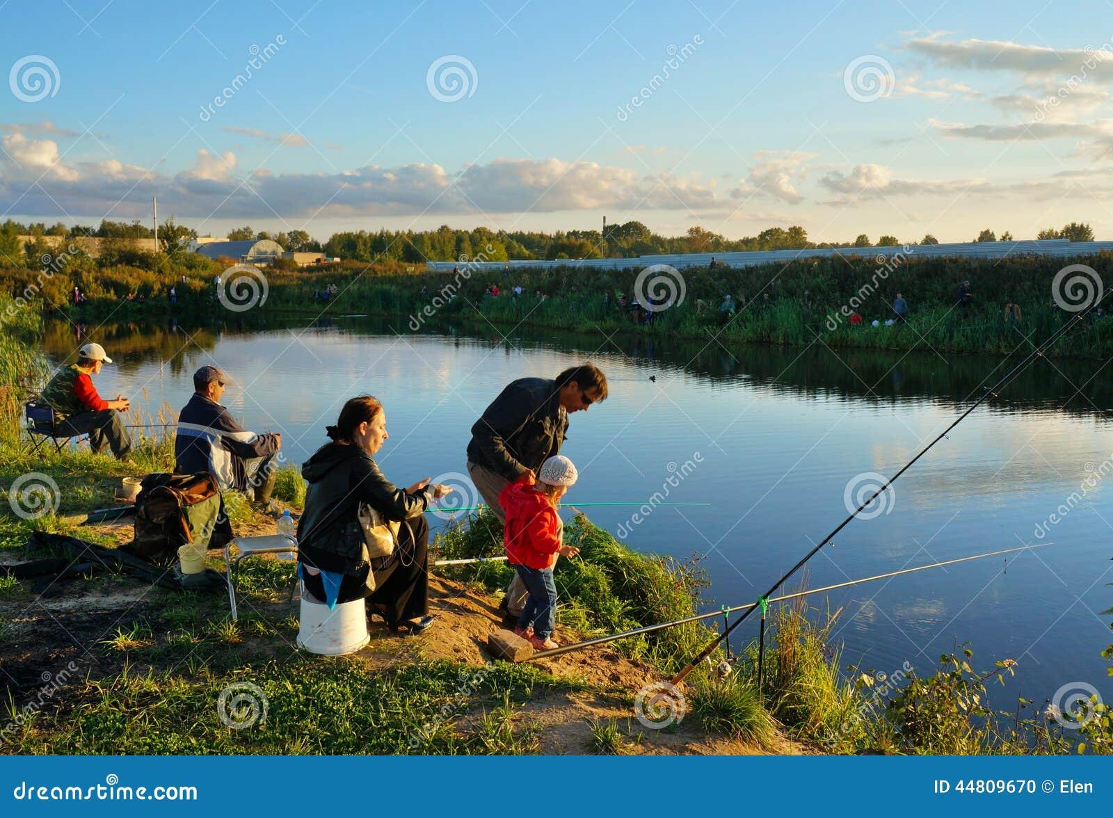 Competencias de deportes en la pesca en la cogida de una carpa y de un esturión, pescadores en el lago