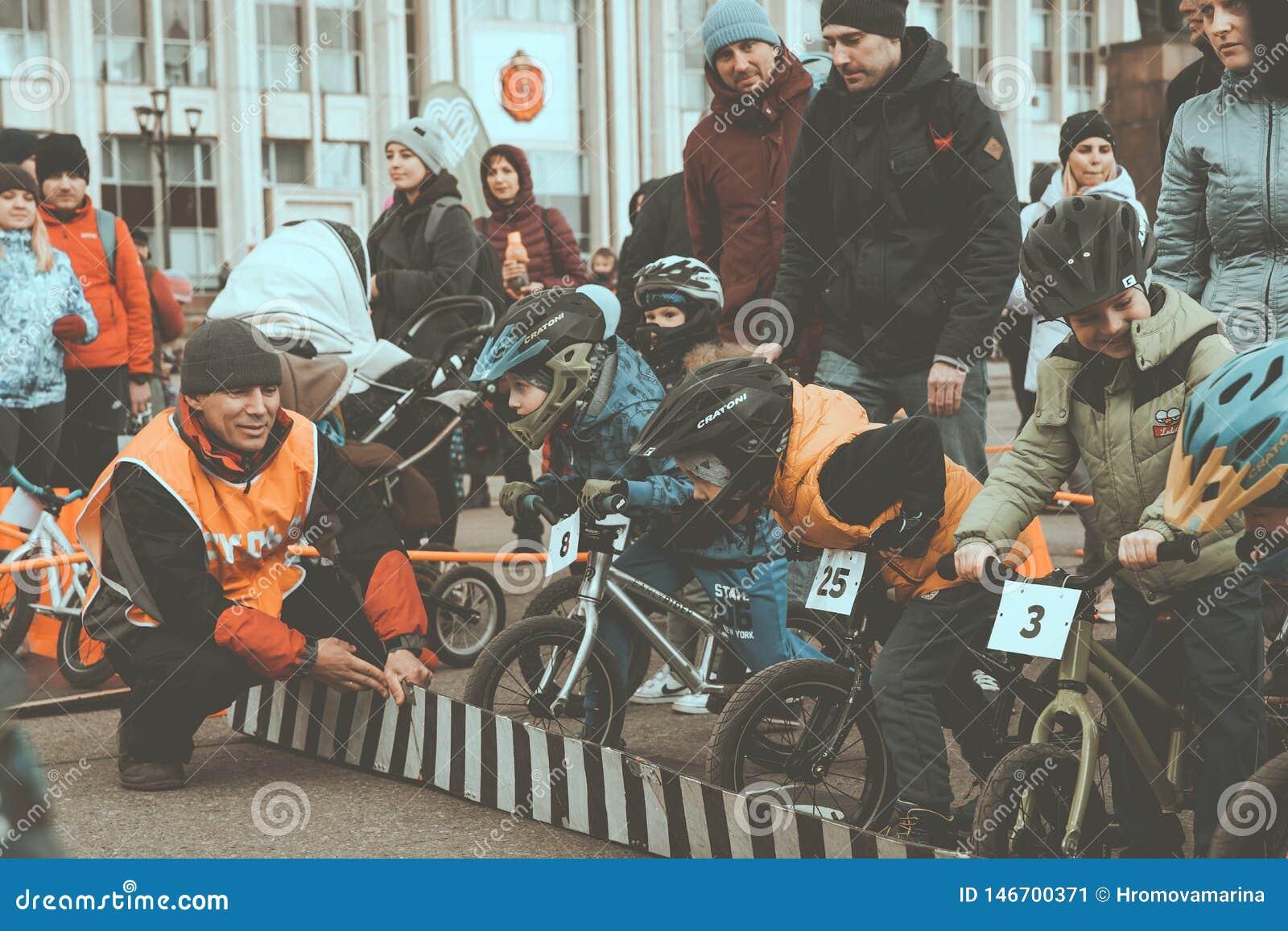 A competi??o amadora das crian?as equilibrar a bicicleta no quadrado de Lenin, grupo de Reade vai