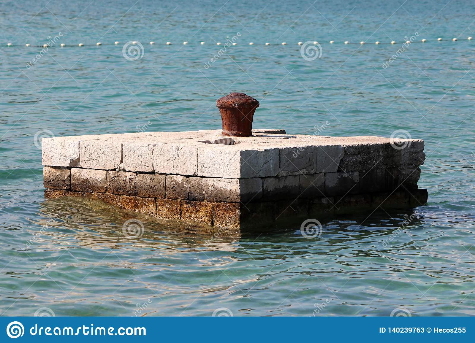 Completely rusted dilapidated iron mooring bollard in middle of stone pier surrounded with calm sea used for tying larger ships