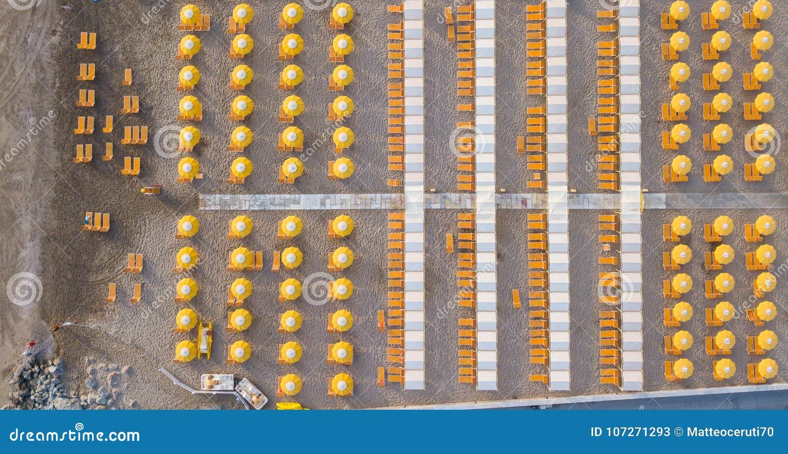 Completi giù la vista aerea del fuco degli ombrelli e dei gazebos sulle spiagge sabbiose italiane Riccione, Italia Litorale adria