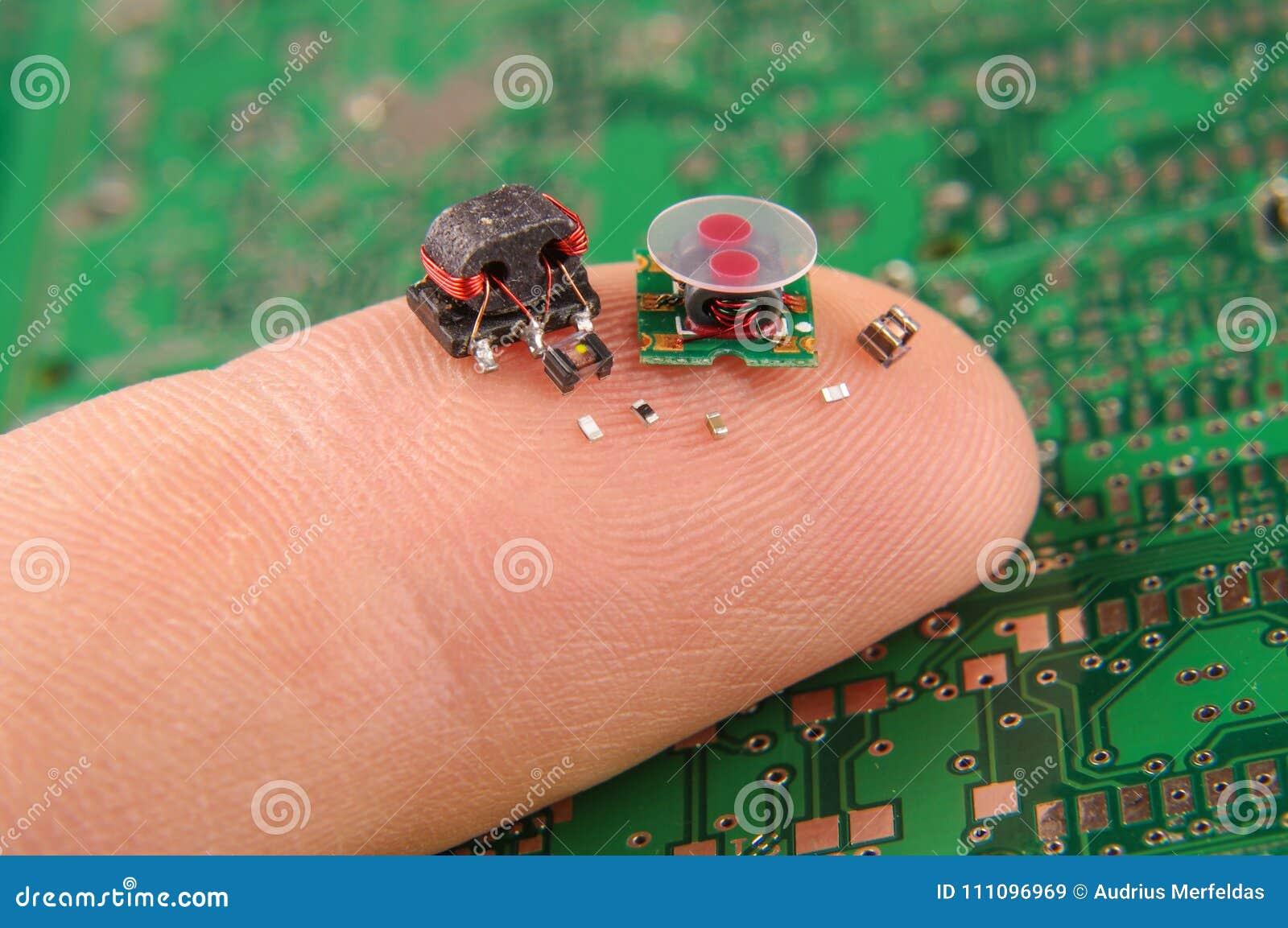 Componentes pequenos da eletrônica no dedo humano