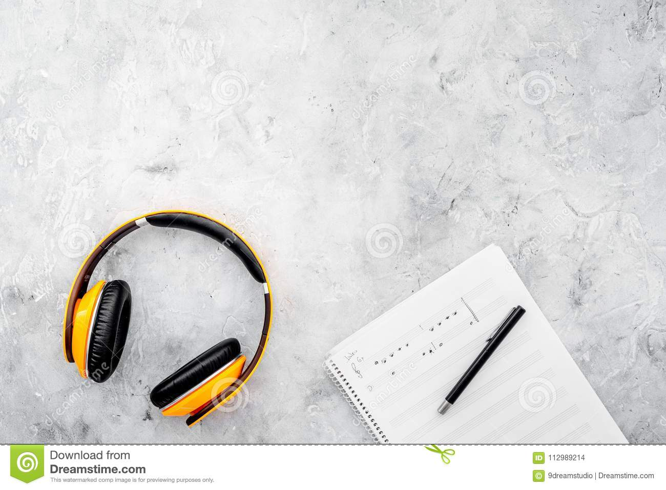 Composer and song writer desktop with headphones and notes on stone background top view mock up