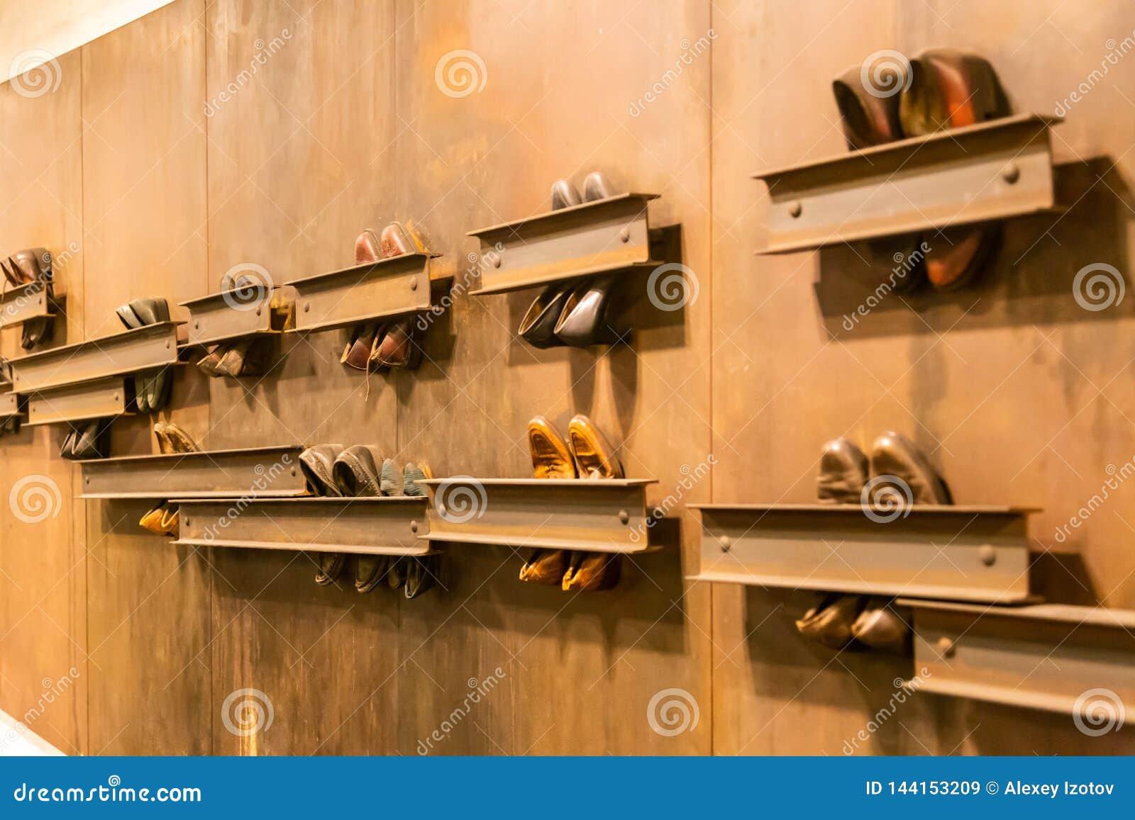 Composição abstrata das sapatas do vintage unidas à parede na passagem da terra