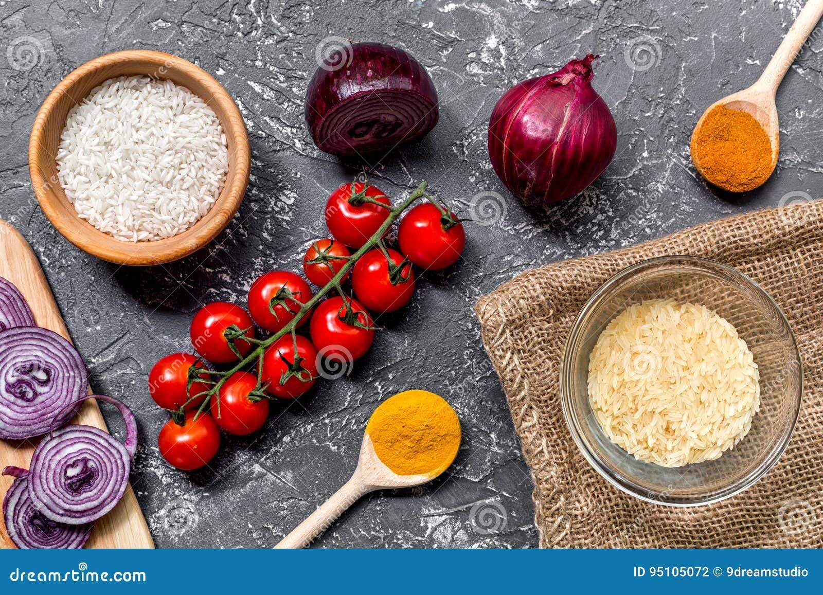 Composição caseiro dos ingredientes do paella com arroz, tomate, cebola na opinião superior do fundo escuro da tabela