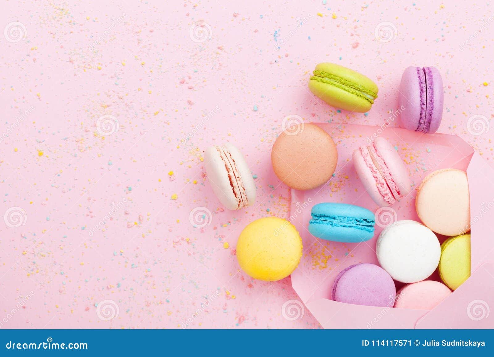 Composição criativa com macaron do envelope e do bolo ou bolinho de amêndoa na opinião superior do fundo pastel cor-de-rosa Confi