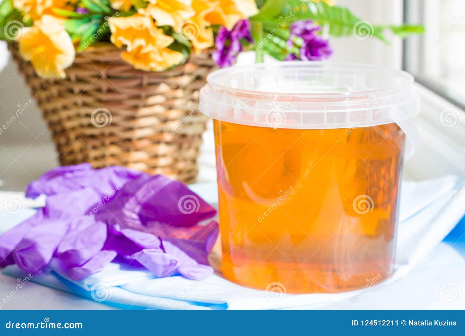 Composição da pasta do açúcar do frasco ou do mel da cera para o cabelo que remove com as luvas e as flores roxas - conceito da d