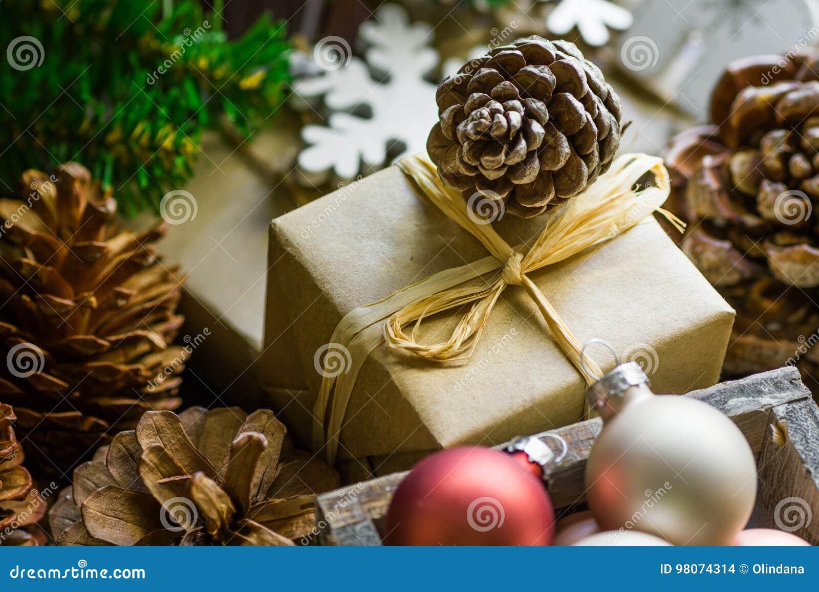 Composição da pilha de caixas de presente no papel do ofício, bolas coloridas do Natal e do ano novo, cones do pinho, ramos de ár