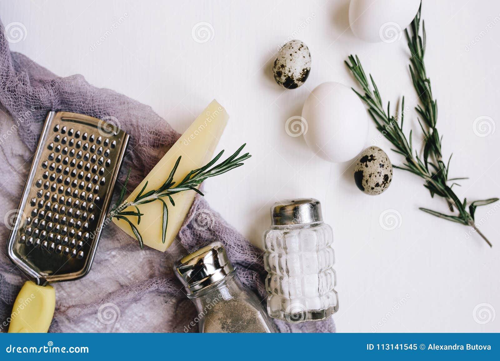 Composição de Flatlay Queijo duro do Parmesão com alecrins, saleiro e pimenta de vidro, ovos e codorniz brancas da galinha, ralad
