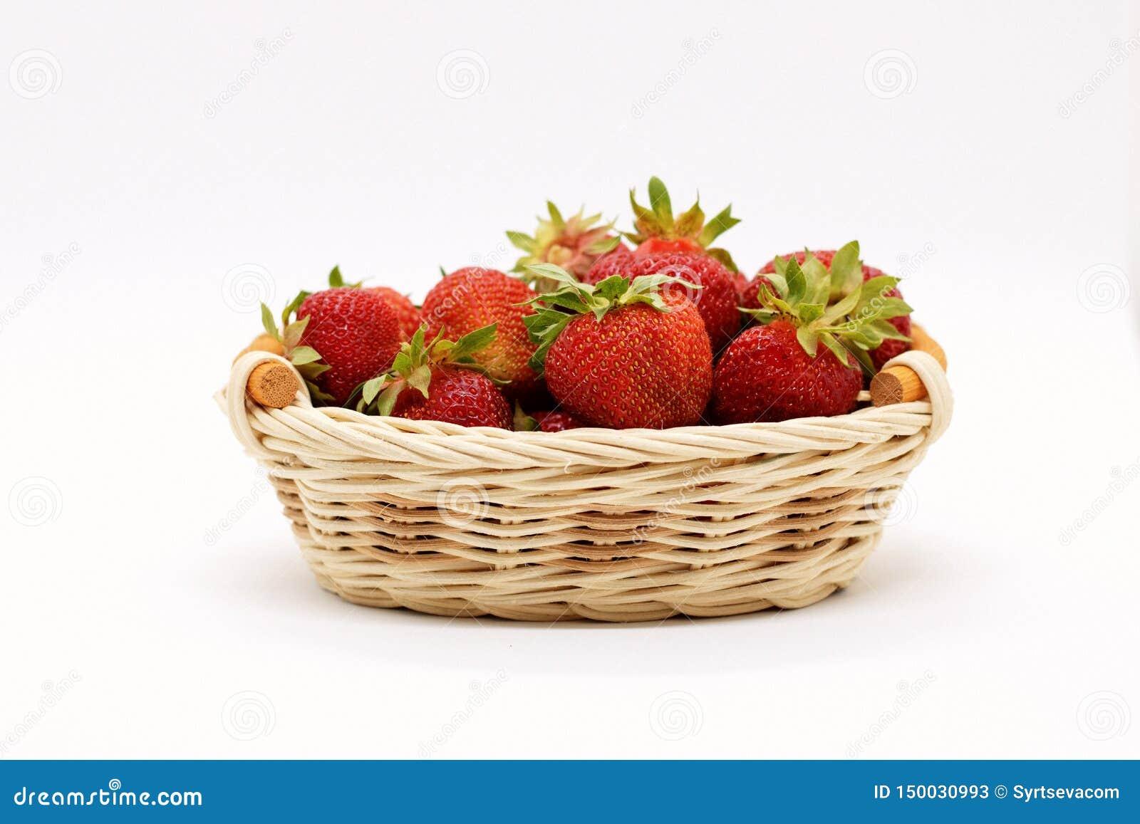 Composição de morangos maduras em um fundo branco em uma cesta de vime