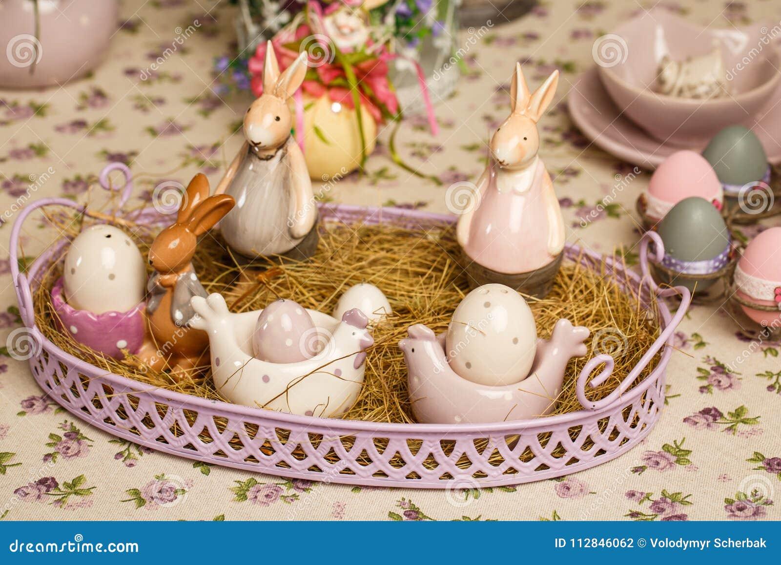 Composição decorativa da Páscoa em um fundo do vintage Mola Um vaso de flores com muscari floresce, os coelhos de uma porcelana,