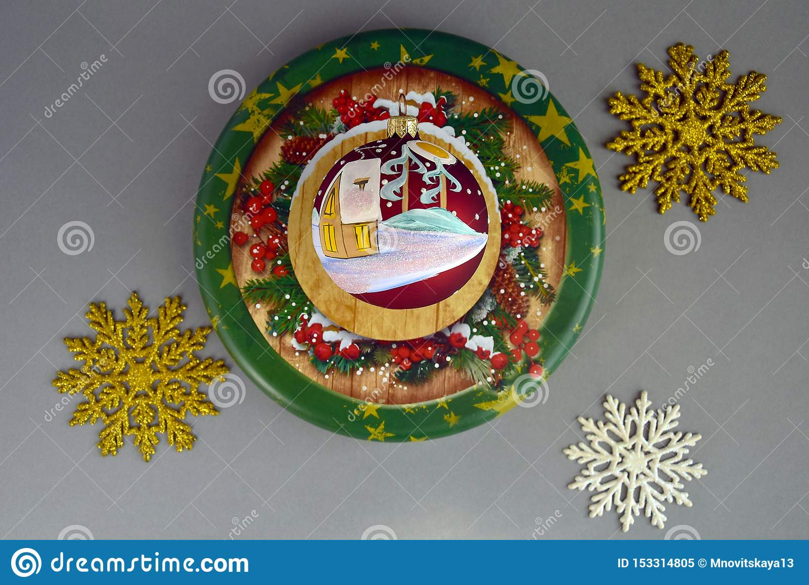 Composição do ano novo no fundo cinzento, Natal, inverno, conceito do feriado Bola do Natal com uma casa coberto de neve pintada