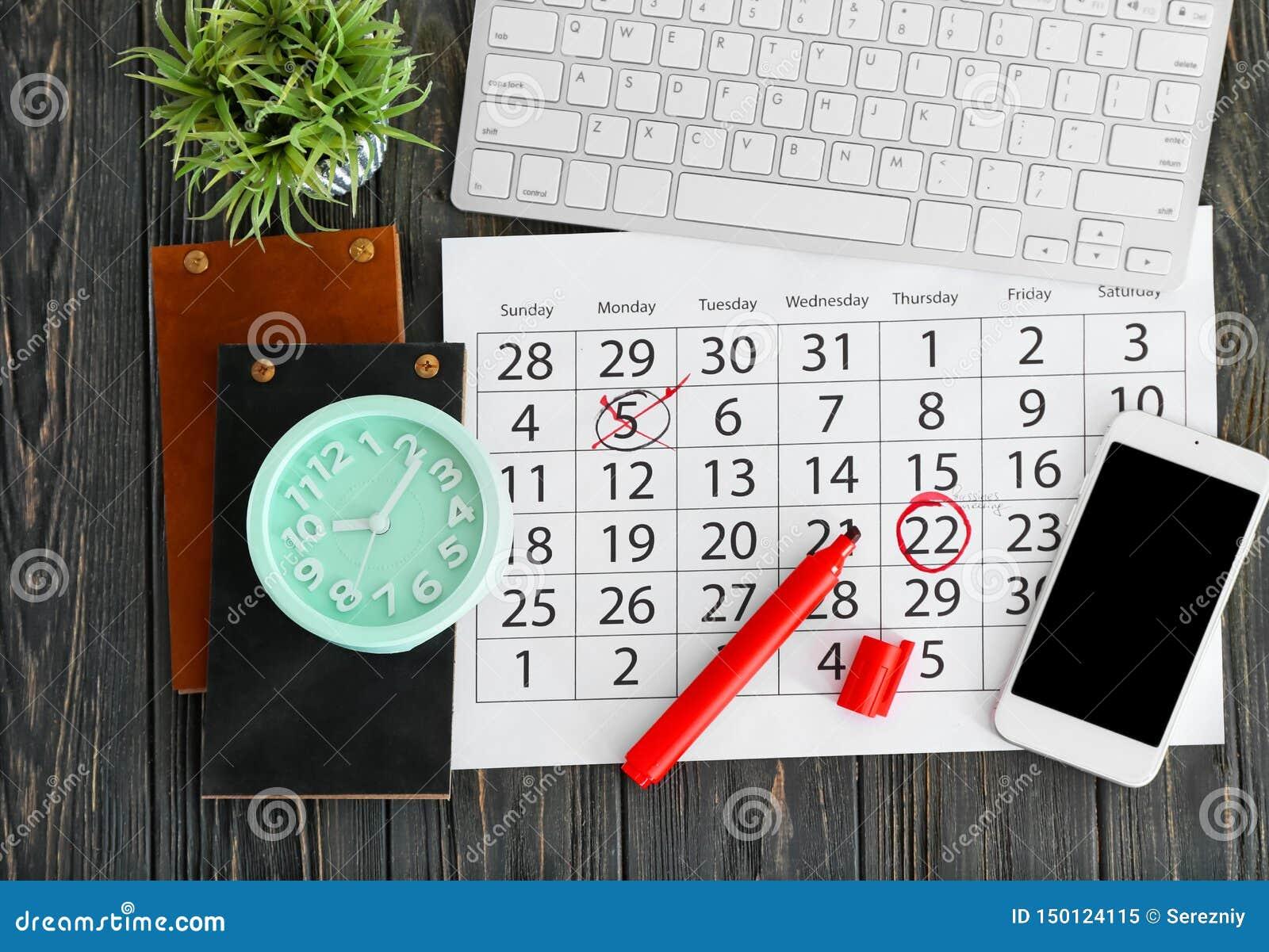 Composição do calendário com notas, teclado de computador e pulso de disparo no fundo de madeira