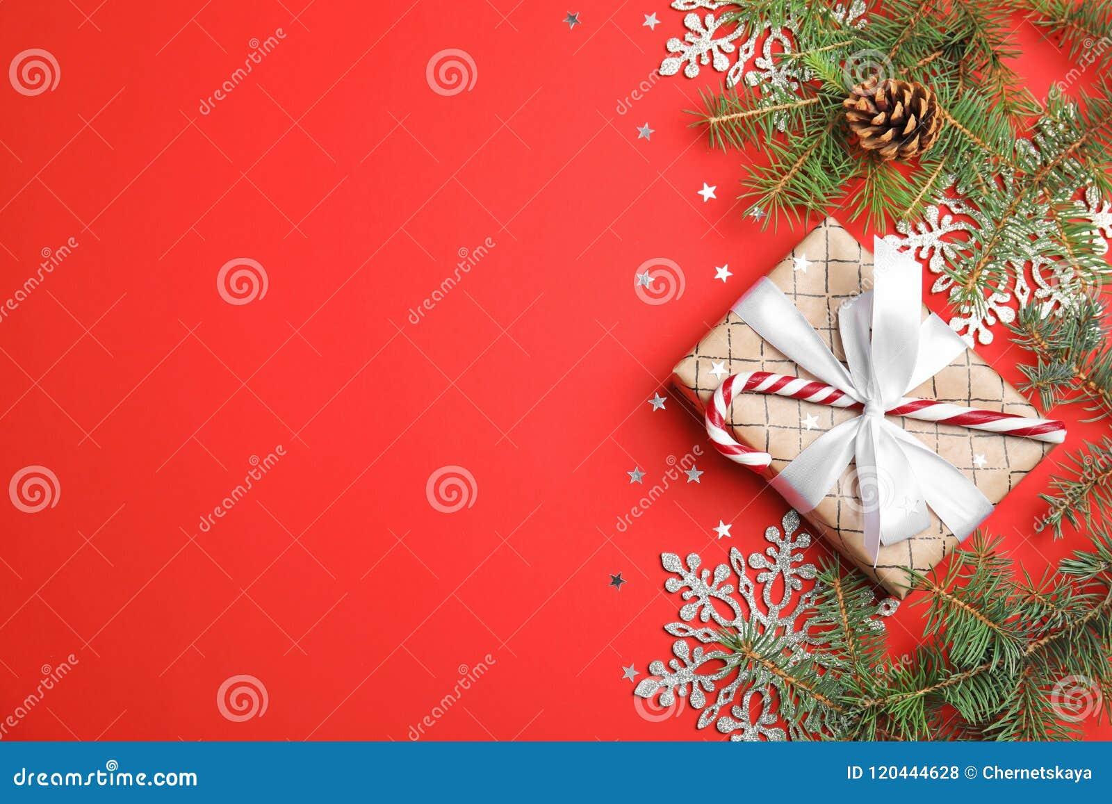 Composição do Natal com caixa de presente e a decoração festiva no fundo da cor