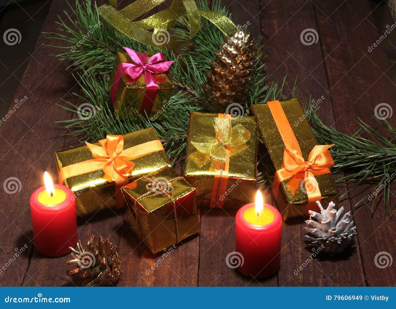 Composição do Natal com conhaque, a caixa de presente e vela de vidro na tabela de madeira