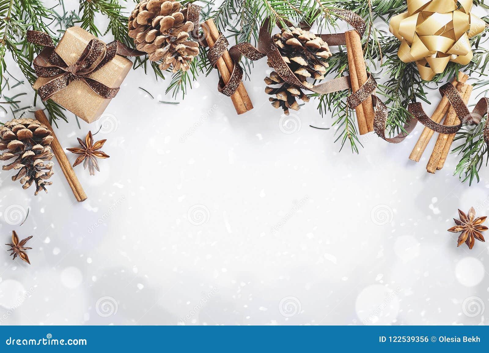 Composição do Natal e do ano novo A caixa de presente com fita, abeto ramifica com cones, anis de estrela, canela no fundo branco