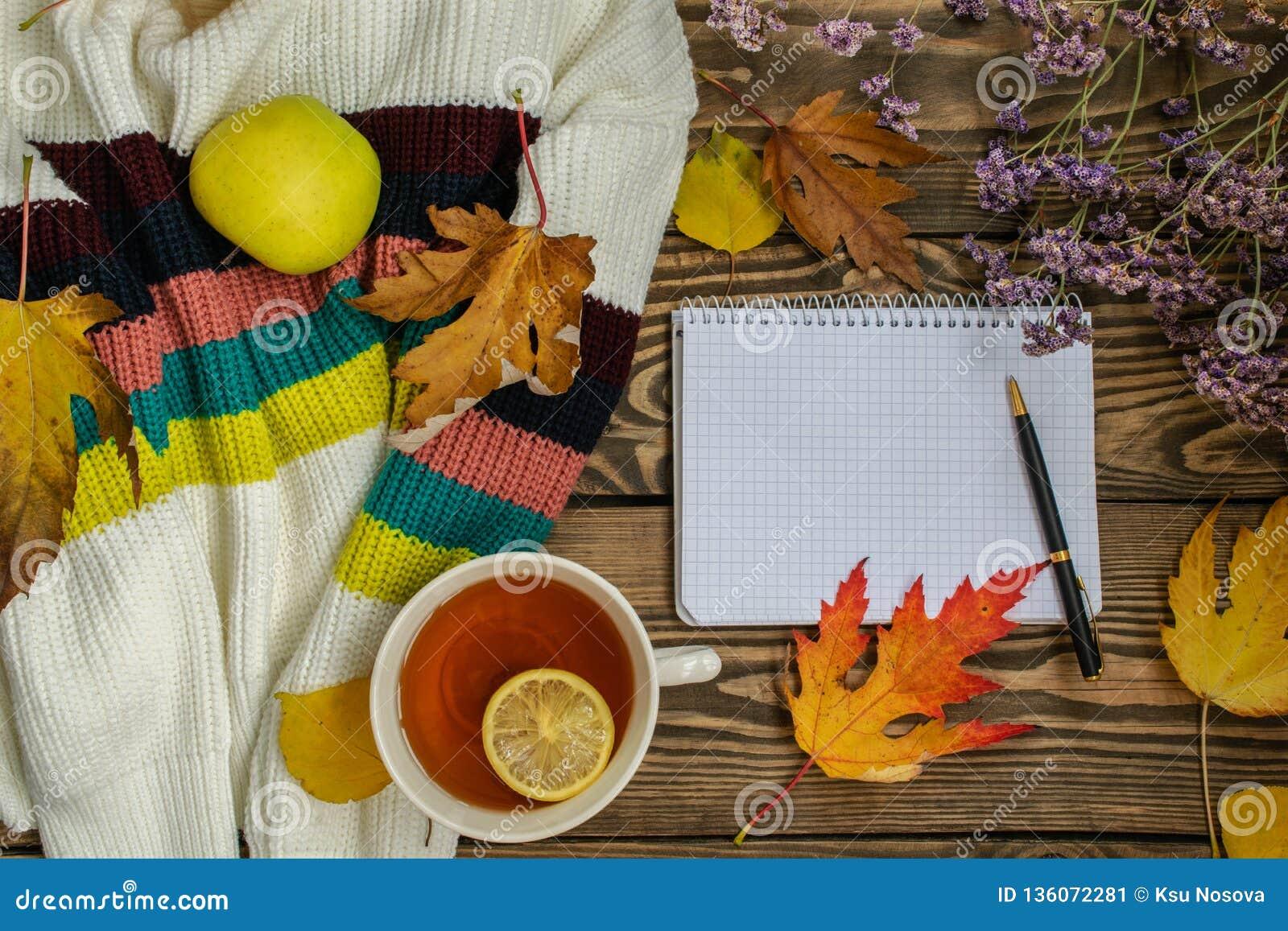 Composição do outono Copo do chá, maçã, folhas de outono secadas, camiseta bege no fundo de madeira