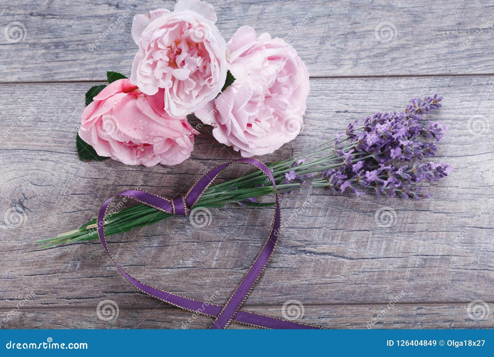 Composição inglesa das rosas da flor festiva com fita, alfazema no fundo de madeira, estilo rústico Vista superior aérea