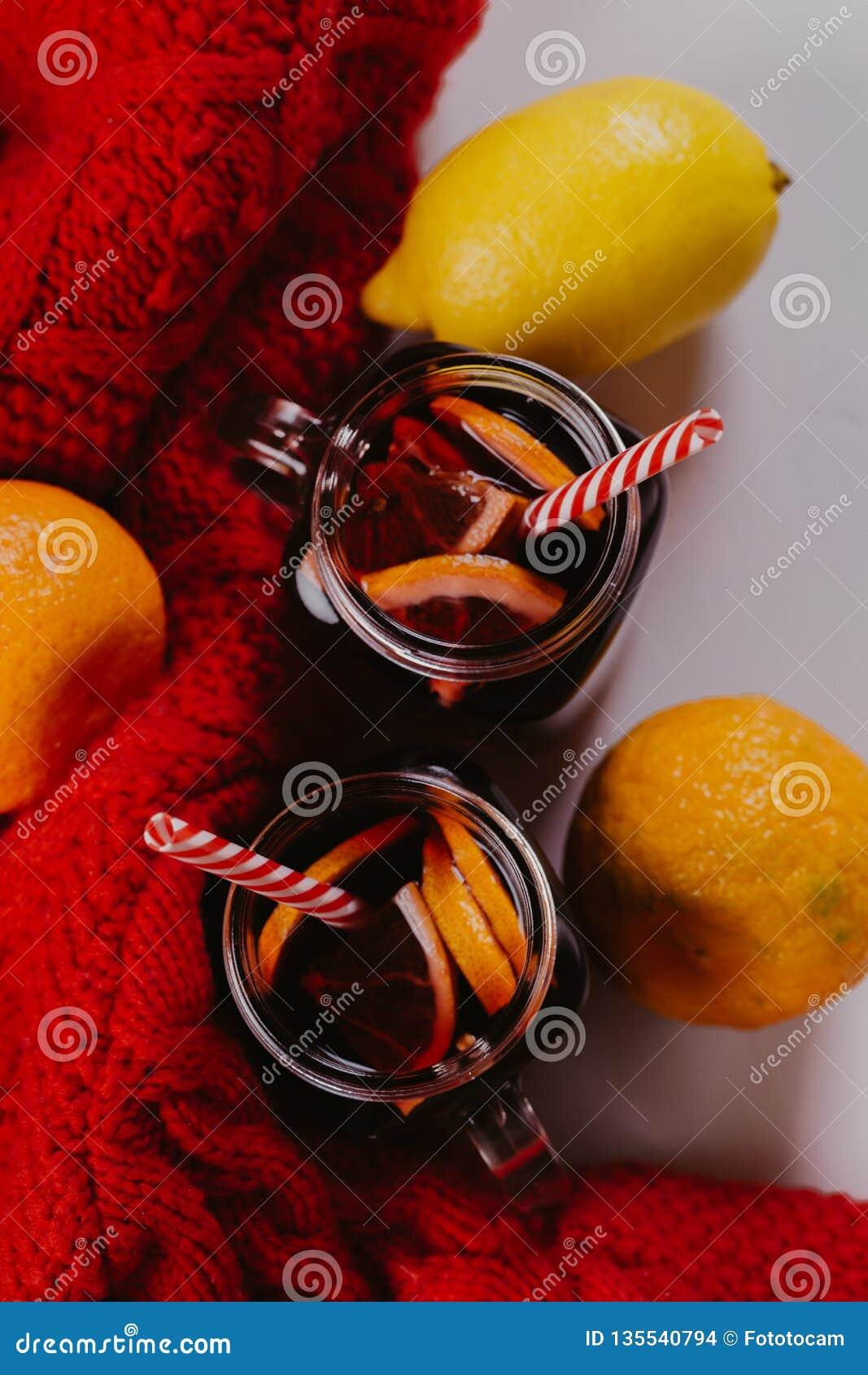 Composición adornada de tazas con el vino reflexionado sobre en bufanda hecha punto, cierre para arriba